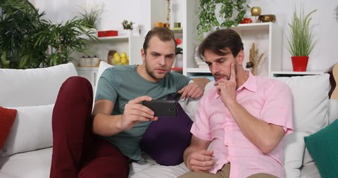 Caucasian Men Laying on the Sofa Viewing a Movie on Mobile Phone Time Relaxation