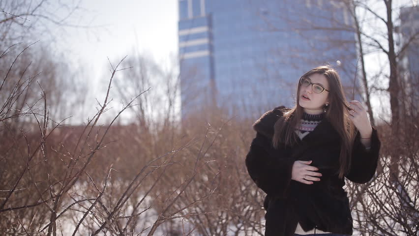 Street emotional portrait of young beautiful woman with glasses in city Model looking at camera. Lady wearing stylish classic winter knitted clothes. | Shutterstock HD Video #1008223948