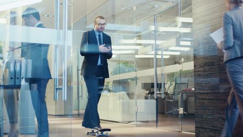 Stylish Suited Businessman Uses Smartphone Rides Skateboard Through the Corporate Building Hallway. Stylish Glass and Concrete Building with Multicultural Crowd of Business People.  RED EPIC-W 8K.