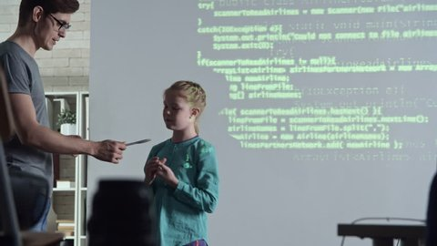 Primary school girl standing in front of class, teacher gives her pointer and asks to show parts of computer code on projector screen