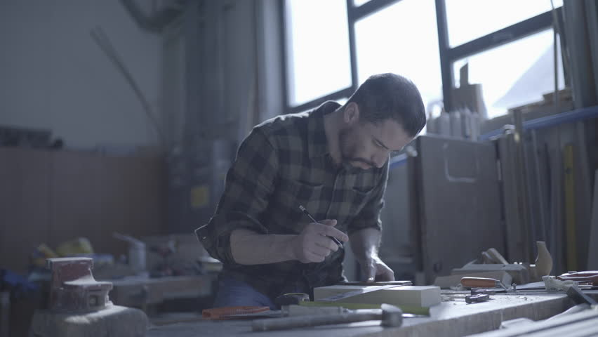 Handsome man in his fourties working in his workshop with wooden tools, like a saw and a drill machine  in the backlight one weekend  | Shutterstock HD Video #1008256888