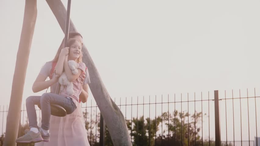Mother pushes daughter on a playground rope swing. Slow motion. Happy girl rides a long zipline wire. Family bonding. | Shutterstock HD Video #1008267058