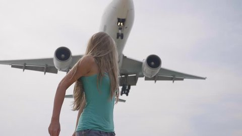 Young woman raising hands up watching at sky with plane,airplane passing overhead, young happy girl watching waving and jumping. Happiness, freedom and vacation concept.
