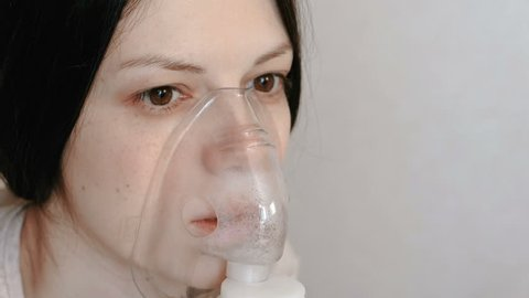 Use nebulizer and inhaler for the treatment. Closeup woman's face inhaling through inhaler mask. Front view