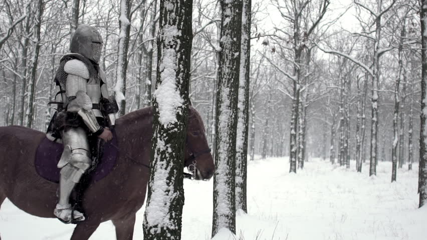 Lone medieval soldier armed with steel weapon riding on dark horse through winter forest, under snowfall in slow motion. Reconstruction of ancient times