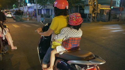 NHA TRANG, VIETNAM - FEBRUARY 28 2018: asian mother rides motorbike with two little daughters
