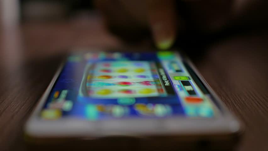 Casino slot machine app on mobile screen against  hand of man using smartphone. Gambling addicted man in front of online casino slot-machine on mobile phone. Screen is blurred. Closeup. 4K UHD. | Shutterstock HD Video #1008321478