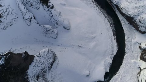 Birds eye looking down and flying over a river in a snow covered canyon/valley. Steep cliffs and dark water, pristine snow.