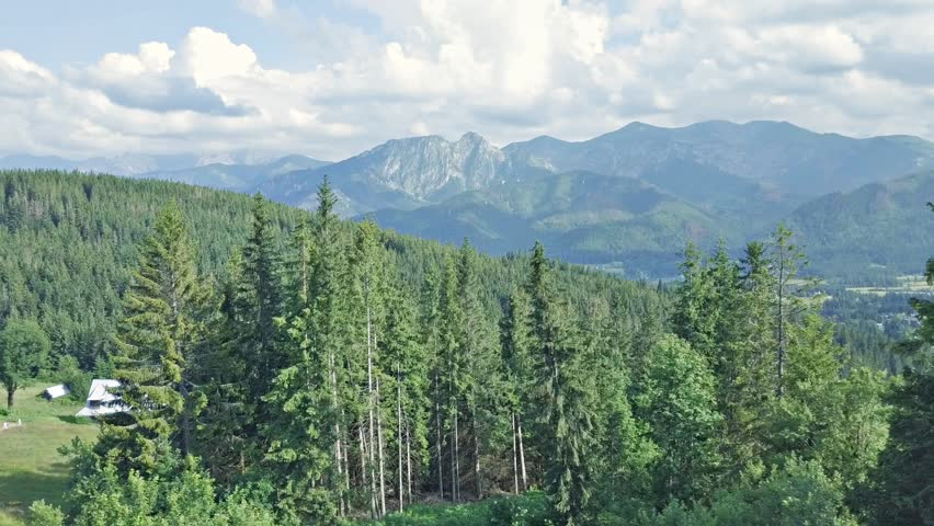 Inspiring Mountains Landscape Panorama from Drone flying lefto to right, beautiful day in summer Tatras, mountain ridge over blue sky in Zakopane, Poland