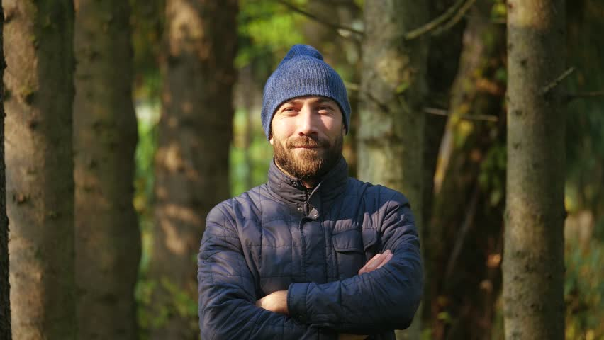 Portrait attractive bearded man standing in a outerwear and knitted hat. Happy smiling young guy crossing his arms looking at camera. nature background #1008348298