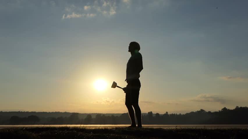 Blond man raises his champion bowl on a lake bank at sunset #1008356158