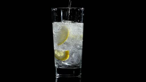 water with lemon and ice in a glass on a black isolated background