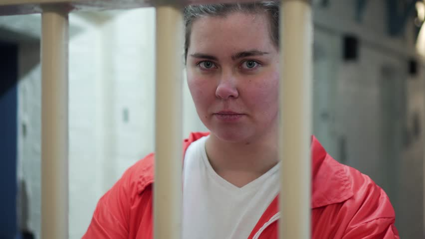 Portrait Of Female Prisoner Behind Bars, Incarceration In Modern Prison, 4K Inmate Locked Up. Part Of A Collection With A Variety Of Camera Angles, With And Without Inmates, Guards.