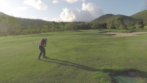 A man playing golf on a lush green golf course.