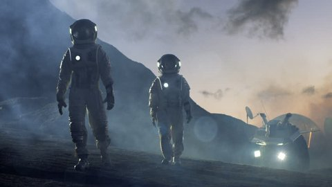 Two Astronauts in Space Suits Confidently Walking on Alien Planet, Exploration of the the Planet's Surface. In the Background Research Base/ Station and Rover. Space Travel, Colonization Concept. 4K.