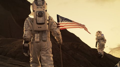 Following Shot of the Two Astronauts Exploring Mars/ Red Planet. One Cosmonaut Carries American Flag. Technological Advance Brings Space Exploration, Travel, Colonization Concept. RED EPIC-W 8K.