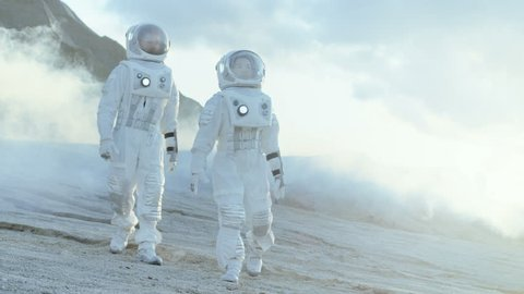 Two Astronauts in Space Suits Confidently Walking on Frozen Alien Planet, Exploration Expedition on the Planet's Surface. Space Travel, New Worlds Discovery, Colonization Concept. Slow Motion. 4K UHD.