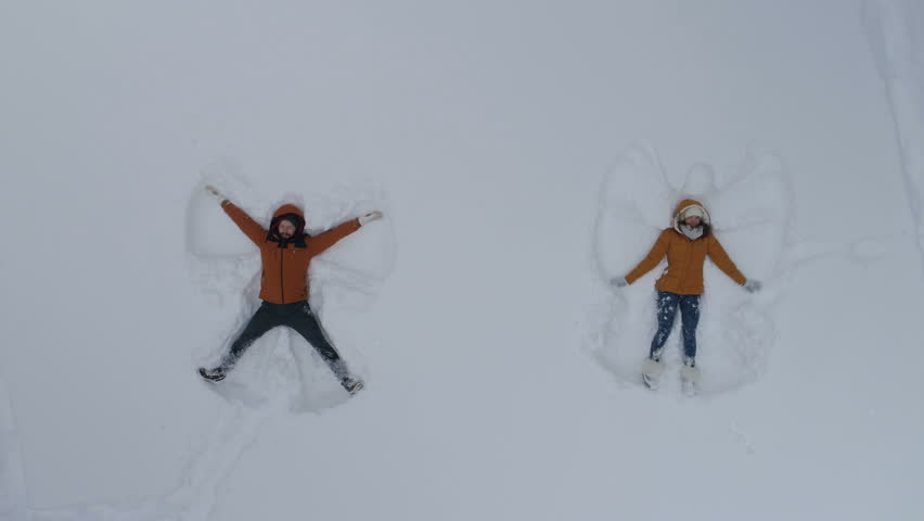 Young man and woman making snow angels
