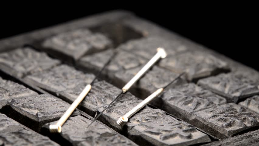 acupuncture needles on antique Chinese wooden print letters