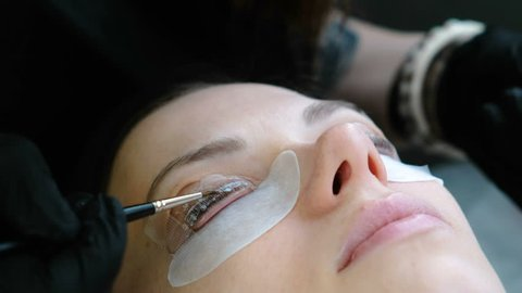 Beauty treatment. Beautician put a solution on curler eyelash curler. and lash lamination. Closeup face.
