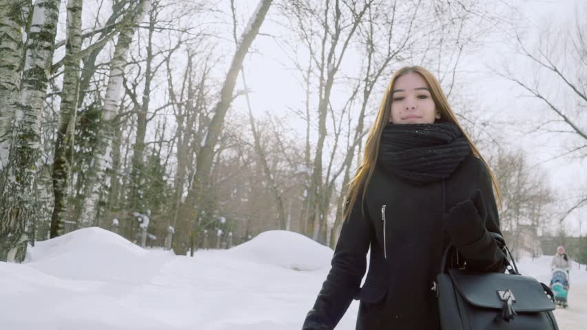 Winter portrait of a young woman. A girl without a headdress walks through the winter park.