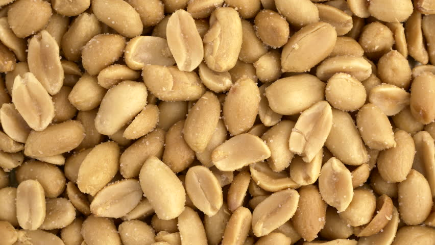 Roasted salted peanuts closeup macro revolving on a turntable. Overhead view. Not loopable. Colors out of camera. No color grading. | Shutterstock HD Video #1008440878