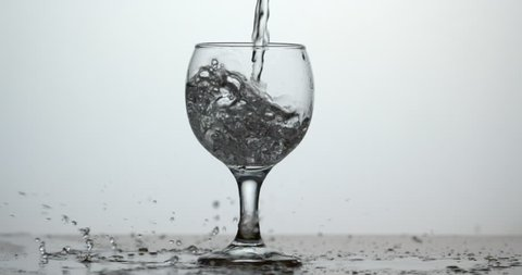 Water pouring into wine glass with frozen spillage drops cinemagraph