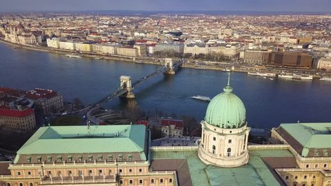 Budapest, Hungary - 4K aerial footage of drone flying up at Buda Castle Royal Palace with Szechenyi Chain Bridge and Parliament of Hungary at background with sightseeing boat on River Danube