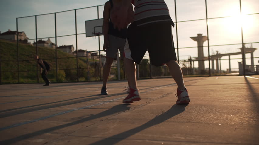 Group of Caucasian males playing streetball dribbling passing having fun. Footage in slowmotion with sun flare