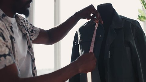 Professional Afro-American tailor taking measures with measuring line on mannequin while crafting a new fashion collection. Light, comfortable studio. Workmanship, working hard. Slow motion, male
