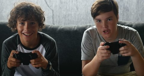 Two friends or brothers smiling and having fun playing a video game with controllers on a couch