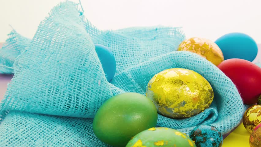 Easter beautiful colorful eggs lie on blue fabric and on yellow and pink surface. Easter eggs in yellow bowl, stand in stands, white background from behind. Beautiful Easter composition made of eggs.