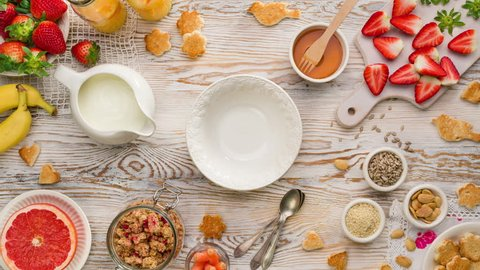 Granola with natural yogurt, fresh strawberries, honey and seeds delicious breakfast or dessert, top view. Healthy eating concept. Stop motion animation.