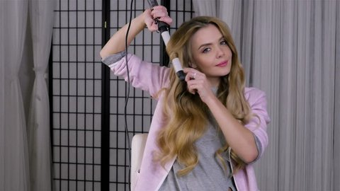 young blonde woman Curling her hair on tongs, doing her hair styling