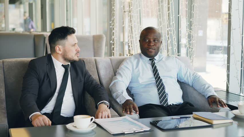 Two multi-ethnic businessmen discussing startup ideas in glassy cafe during lunch time. Coffee cup, financial graphs and digital tablet are on table | Shutterstock HD Video #1008509038