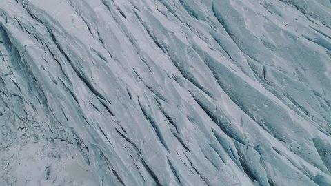 Birds eye aerial shot flying slowly over a pristine glacier. Interesting texture pointed straight down at the icy landscape.