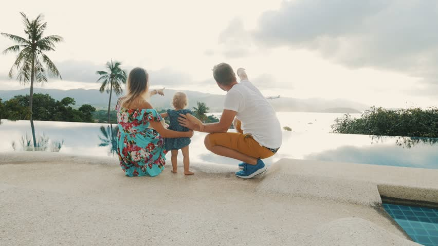 Happy family on outdoor balcony with infinity pool and plane flying in sky