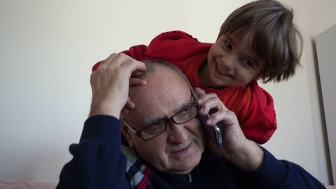 4K Kid bothers his grandfather while speaking on phone