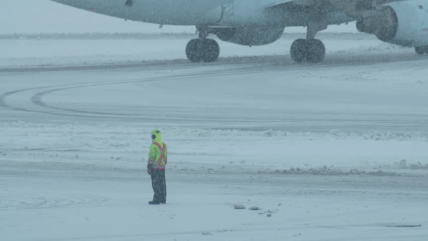 An aircraft marshaller stands along a runway in a snow storm as a commercial airplanees along in the background