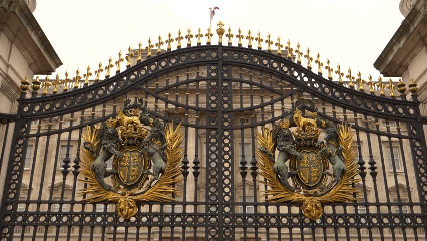 Gate at Buckingham Palace, London, England with british flag on the rooftop of the palace , slow motion