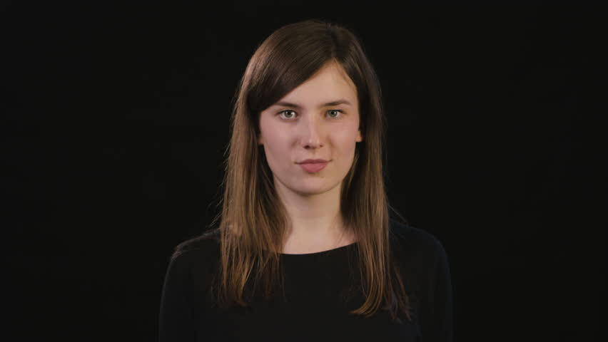 A beautiful young lady showing a shhh meme against a black background. Medium Shot