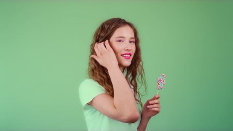 Beautiful young girl on a colored background having fun with lollipop