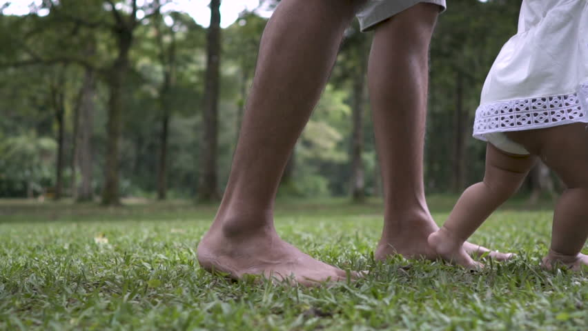 father support his daughter to walk her first step on grass #1008595708