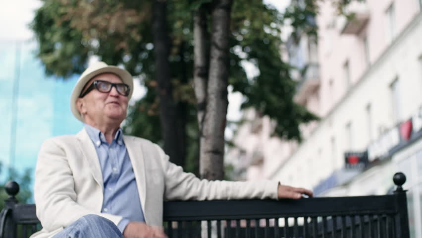 Medium shot of senior man in hat and glasses sitting on bench and greeting his old friend with a hug