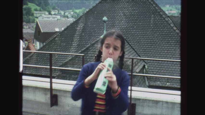 FLAWIL, SWITZERLAND, MAY 1977. Young Greek Girl Plays Melodica On The Balcony And Dances