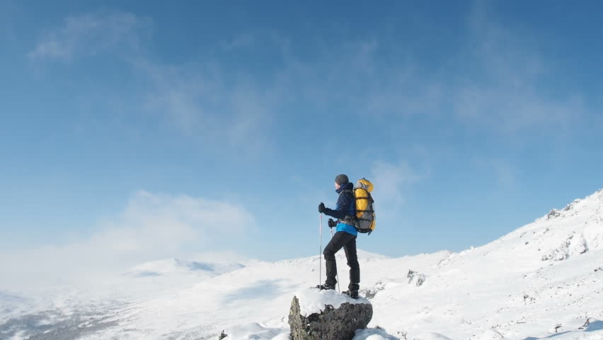 Young Hiker Man Standing On Top Of The Mountain. Mountain Alps Mountaineering Snow Climbers Travel. Man Raising Hands On Mountain Top Winner Concept. Hiker Man Trekking Snow Moutains Climbing .
