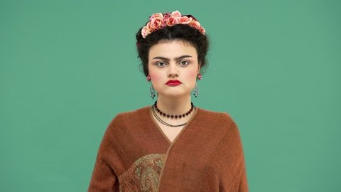 Portrait of woman with thick eyebrows and red lips makeup as Frida Kahlo wearing roses in hair and looking strictly on camera, isolated over green background. Stylization concept