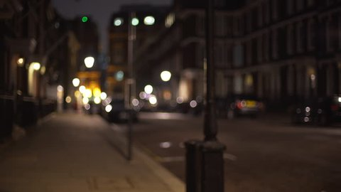 Left to right pan of empty residential street in London in evening. Defocused shot of empty urban street, people tucked in for the night at home. 4k