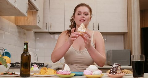 The curvy sad woman is nervously destroying the cupcake and emotionally shouting. Kitchen location. Table full of cakes and junk food.