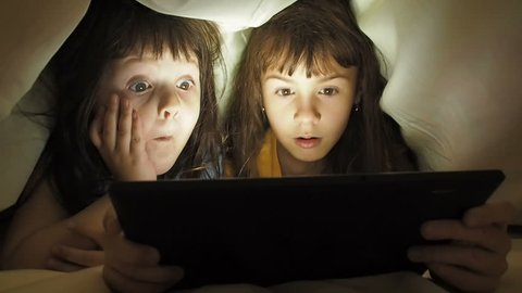 Children with a tablet under the blanket. Children at night with a tablet. Little girls with a tablet in the bedroom.